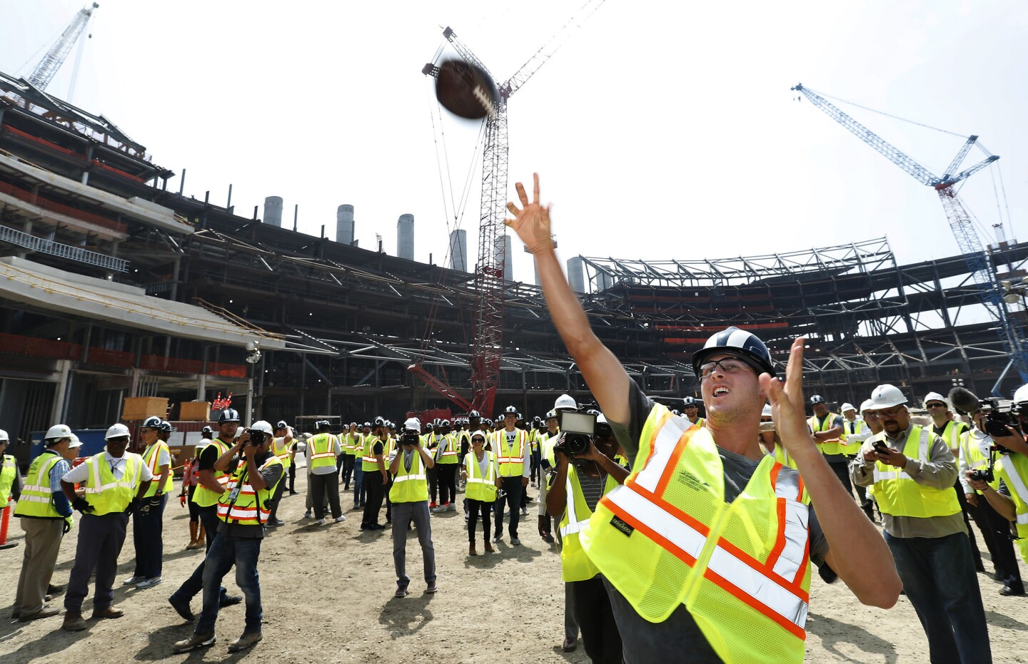 Rams quarterback Jared Goff tosses a football up to construction workers in one of the decks above, during a tour of Los Angeles Stadium at Hollywood Park in Inglewood, the future home of the Rams. Instead of practice on the final day of minicamp, the Rams players and coaches boarded buses and headed to the stadium under construction in Inglewood.
