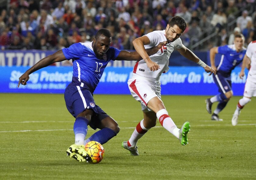 FILE - In this Friday Feb. 5, 2016, file photo, United States' Jozy Altidore, left, tries to shoot at goal as Canada's Steven Vitoria vie defends during the first half of an exhibition soccer match in Carson, Calif. Altidore got his season off to an outstanding start with goals in each of the Ameri