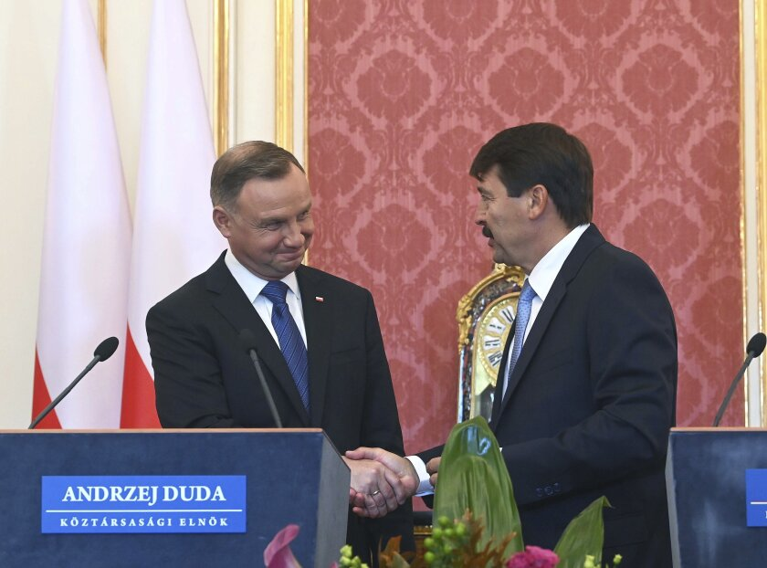 Polish President Andrzej Duda, left, and his Hungarian counterpart Janos Ader, right, shake hand after a joint press conference as part of a meeting at Alexander Palace in Budapest, Hungary, Thursday, Sept. 9, 2021. (Noemi Bruzak/MTI via AP)