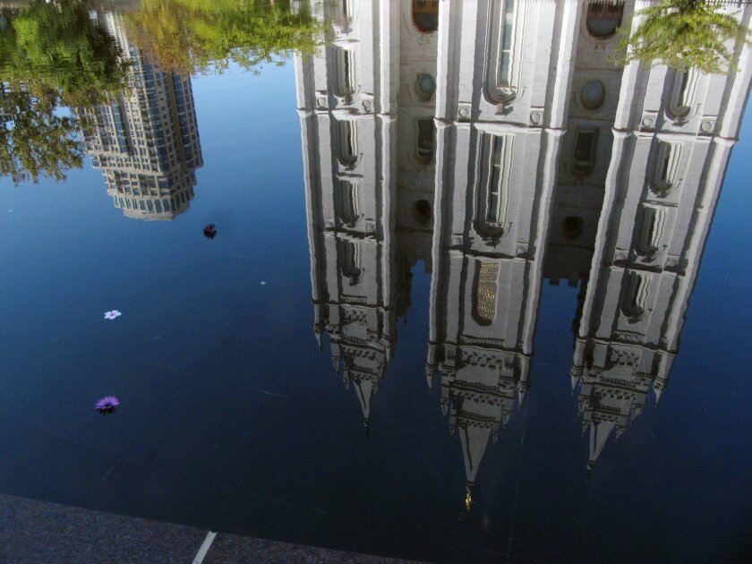 FILE - In this Sept. 30, 2012, file photo, the Mormon temple in Salt Lake City is reflected in a pool. A newly-posted article, part of a series of recent online articles posted on the website of The Church of Jesus Christ of Latter-day Saints, affirms the faith's belief that humans can become like