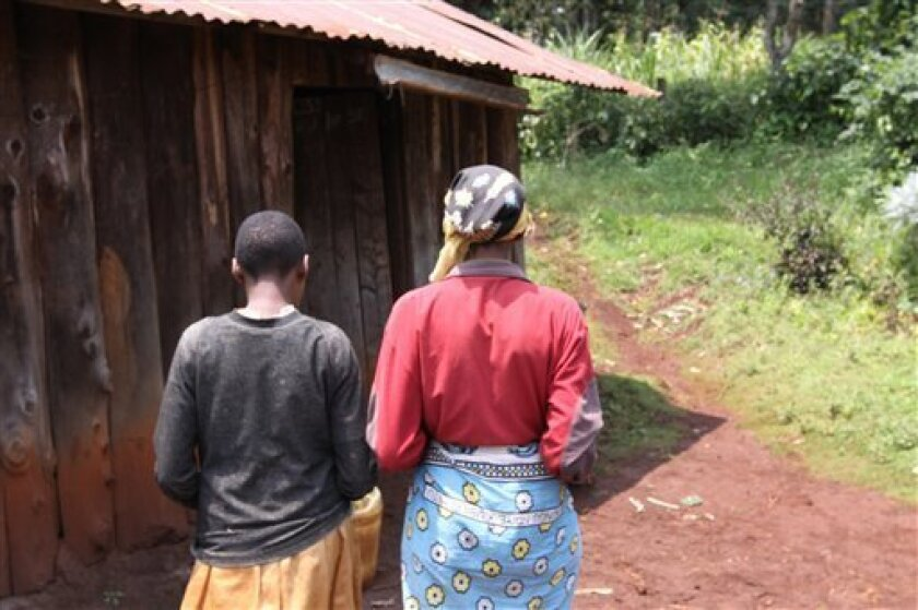 In this Aug. 24, 2010 picture, Emma, right, walks with her daughter towards their house in Kabazi, Kenya. Emma has gone to court every month for 2½ years to try and prove that a neighbor raped her mentally disabled 14-year-old daughter. The process is excruciating. Evidence went missing. The court file disappeared. Officials mock and ignore her. But the illiterate single mother perseveres, encouraged by a new Kenyan government helpline started two and a half years ago to help stop child abuse. (AP Photo/Khalil Senosi)