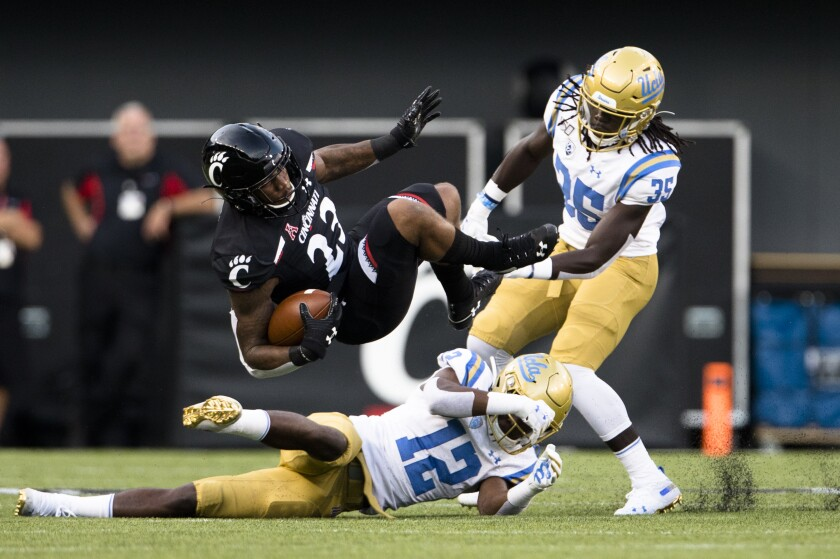 UCLA defensive backs Elijah Gates (12) and Carl Jones (35) bring down Cincinnati running back Gerrid Doaks during the first half of the Bruins' season-opening loss Thursday.