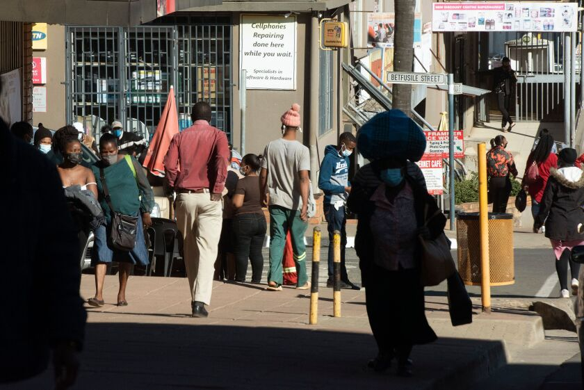 People walk through the city streets of Mbabane on July 3, 2021.