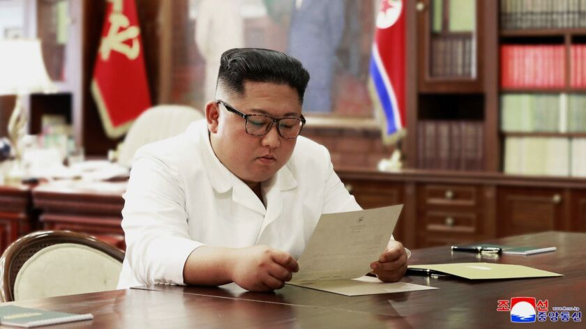 In this undated photo provided on Sunday, June 23, 2019, by the North Korean government, North Korean leader Kim Jong Un reads a letter from President Trump.