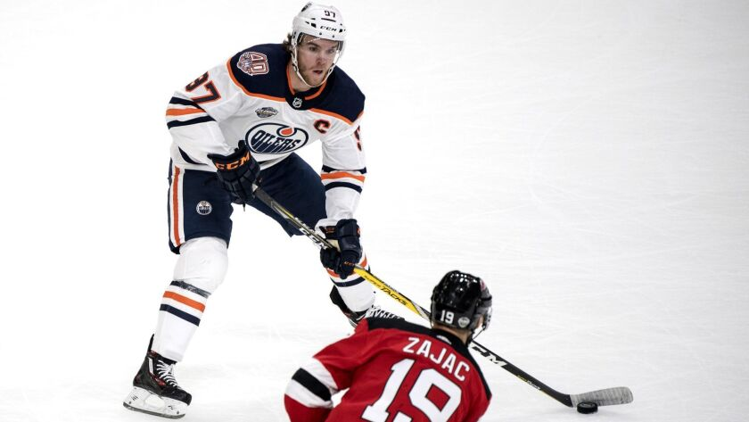 Edmonton Oilers' Connor McDavid, background and New Jersey Devils' Travis Zajac vie for the puck, du