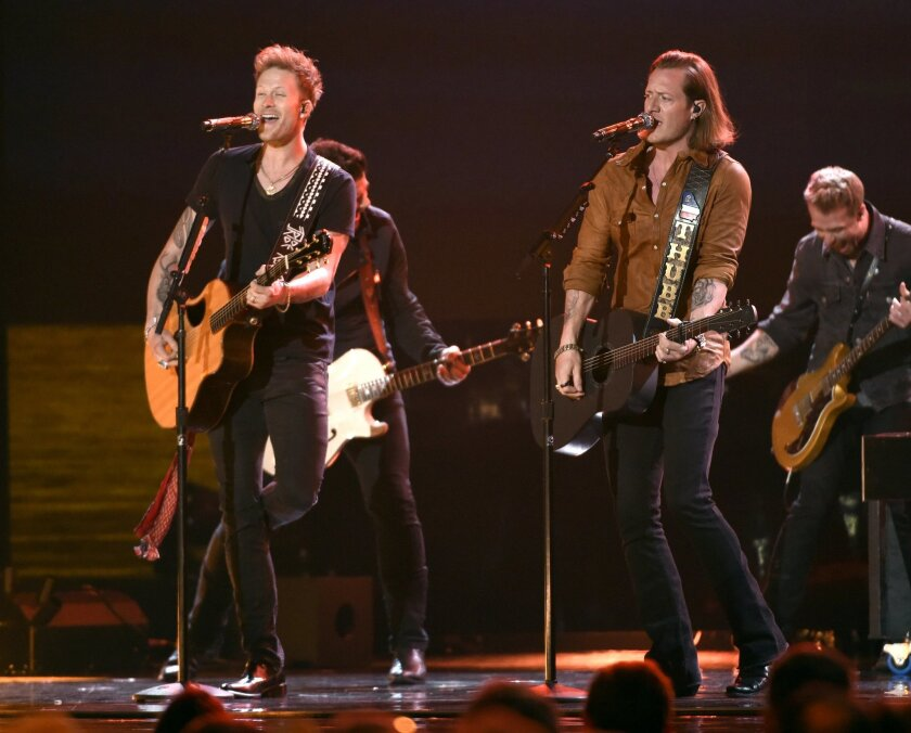 FILE - In this April 19, 2015 file photo, Brian Kelley, left, and Tyler Hubbard, of Florida Georgia Line, perform at the 50th annual Academy of Country Music Awards at AT&T Stadium in Arlington, Texas. CMT is allowing mobile video-streaming application Meerkat to stream the Florida George Line whil