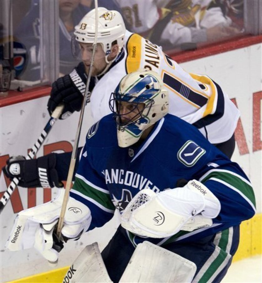 Nashville Predators center Nick Spaling (13) tries to get around Vancouver Canucks goalie Roberto Luongo (1) during the second period of their NHL hockey game, Thursday, March,14, 2013, in Vancouver. (AP Photo/The Canadian Press, Jonathan Hayward)