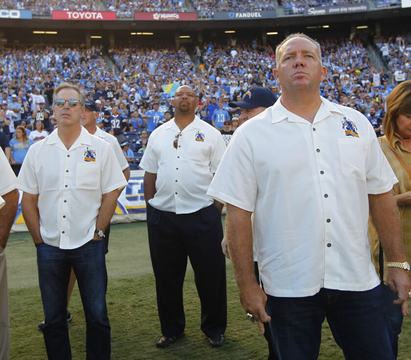 Former San Diego Chargers player Stan Humphries, right, along with Rolf Benirschke, left, and Leslie O'Neal look on during alumni weekend.