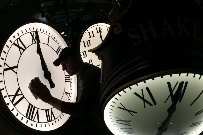 Dave LeMote wipes down a clock at Electric Time Co. in Medfield, Mass., on Friday. Most Americans will set their clocks 60 minutes forward before heading to bed Saturday night.