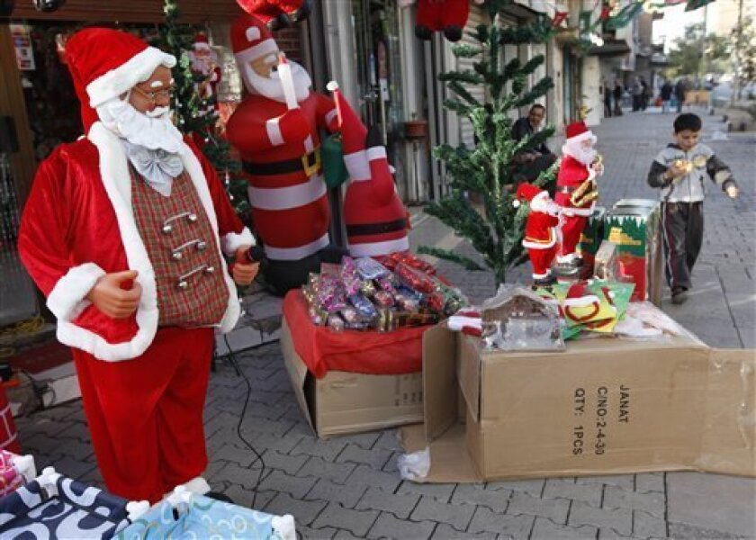 A boy walks past a shop selling Santa Claus items and Christmas decorations in downtown Baghdad, Iraq, Wednesday, Dec. 22, 2010. Church officials in Iraq say they have canceled some Christmas festivities in two northern cities over fears of insurgent attacks. (AP Photo/Hadi Mizban)