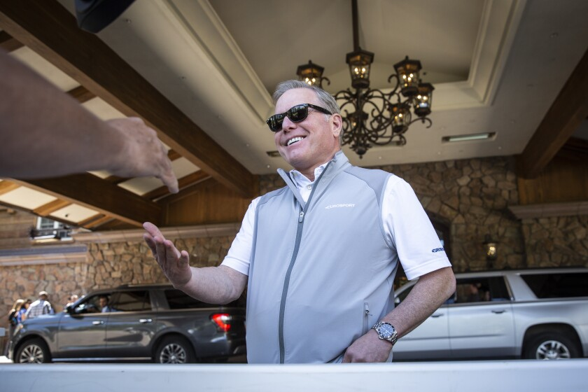 Discovery's David Zaslav in a polo shirt and sports vest in the flagstone entry of a hotel.