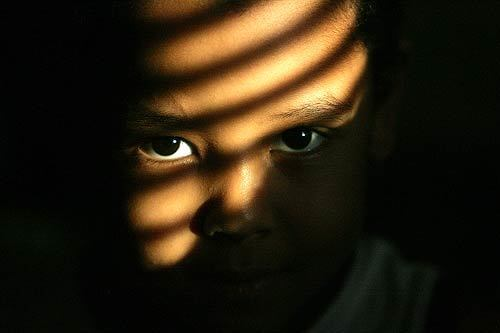 Sudanese refugee Mazine Mohamed, 5, peers through the late-afternoon light from his home in Omaha. Mazine lives with his parents, Abdel Hamid Mohamed and Hayffa Ahmed, and siblings in a two-bedroom apartment.