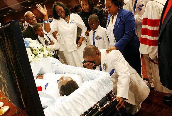 Anita Shaw prays as her husband Jamiel Shaw Sr., kneels at the casket of their son Jamiel Shaw Jr.