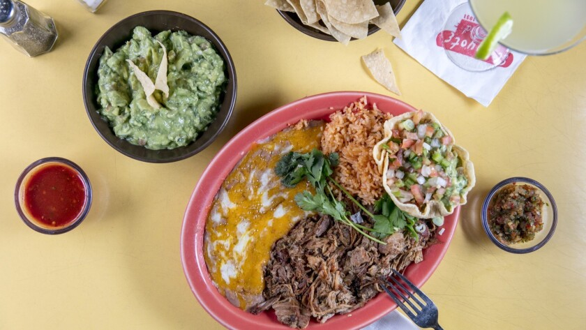 LOS ANGELES, CALIFORNIA - May 18, 2019: The carnitas plate, with a side of guacamole and chips, sal
