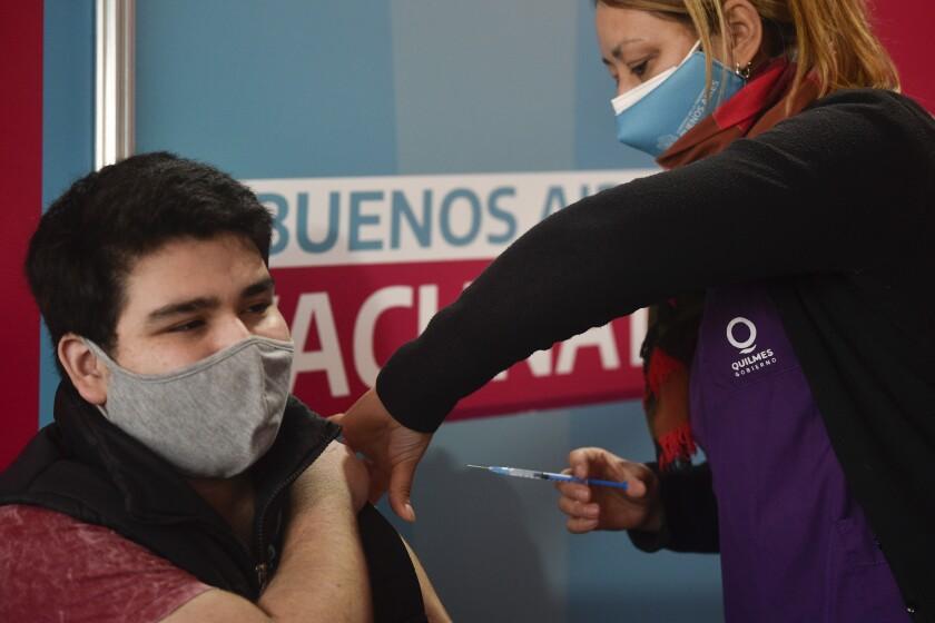 Una trabajadora de salud aplica la vacuna de Moderna contra COVID-19 a un joven