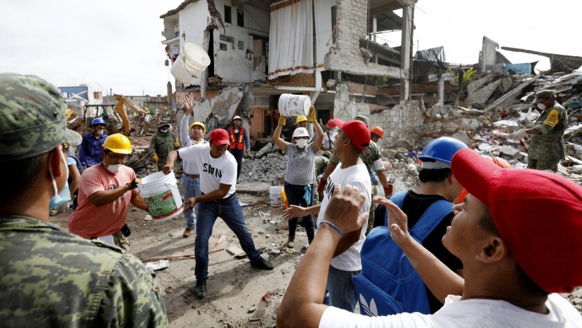 JOJUTLA, MORELOS -- SATURDAY, SEPTEMBER 23, 2017: Volunteers along side the Mexican Military remove
