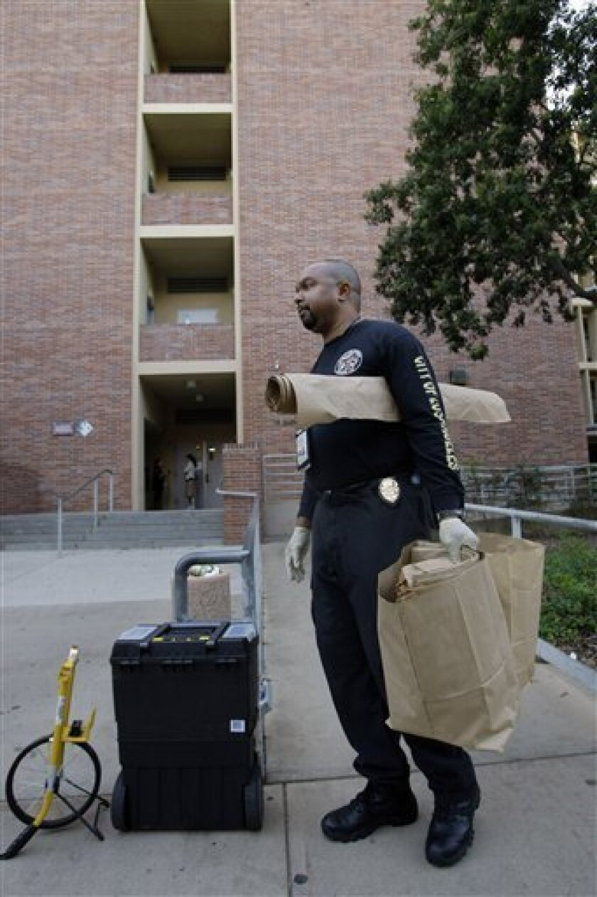 Los Angeles Police Department Scientific Investigation Division criminalist Nand Hart-Nibbrig arrives on the UCLA campus outside Young Hall in Los Angeles on Thursday, Oct. 8, 2009. A female UCLA student was hospitalized Thursday after a fellow student slashed her throat at Young Hall in a chemistry lab on campus, authorities said. A man was arrested after UCLA police got a call about the stabbing Thursday afternoon. (AP Photo/Damian Dovarganes)
