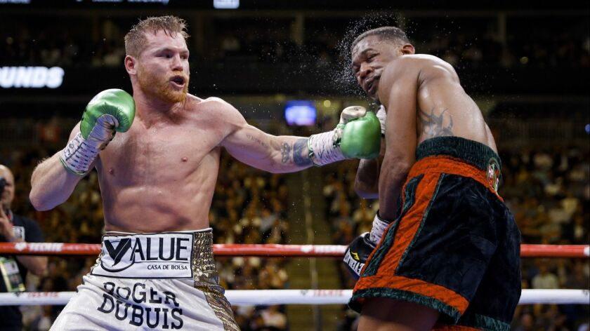Canelo Alvarez, left, of Mexico, hits Daniel Jacobs during a middleweight title boxing match Saturda