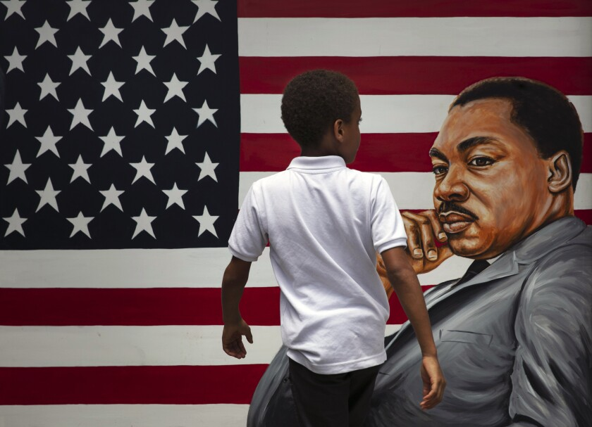 A young boy walks past a painting of Dr. Martin Luther King Jr. during a Juneteenth celebration in Los Angeles. Friday, June 19, 2020. Juneteenth marks the day in 1865 when federal troops arrived in Galveston, Texas, to take control of the state and ensure all enslaved people be freed, more than two years after the Emancipation Proclamation. (AP Photo/Jae C. Hong)