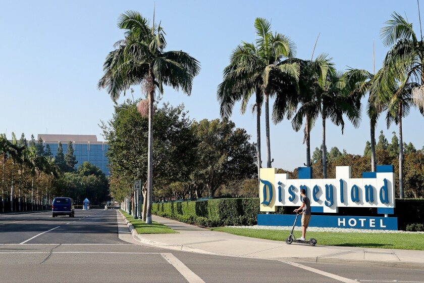 A scooterist cruises by the Disneyland Hotel marquee along Magic Way in Anaheim.