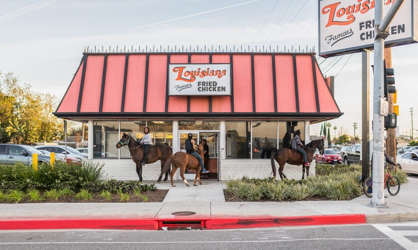 Members of the Compton Cowboys wait outside a restaurant.