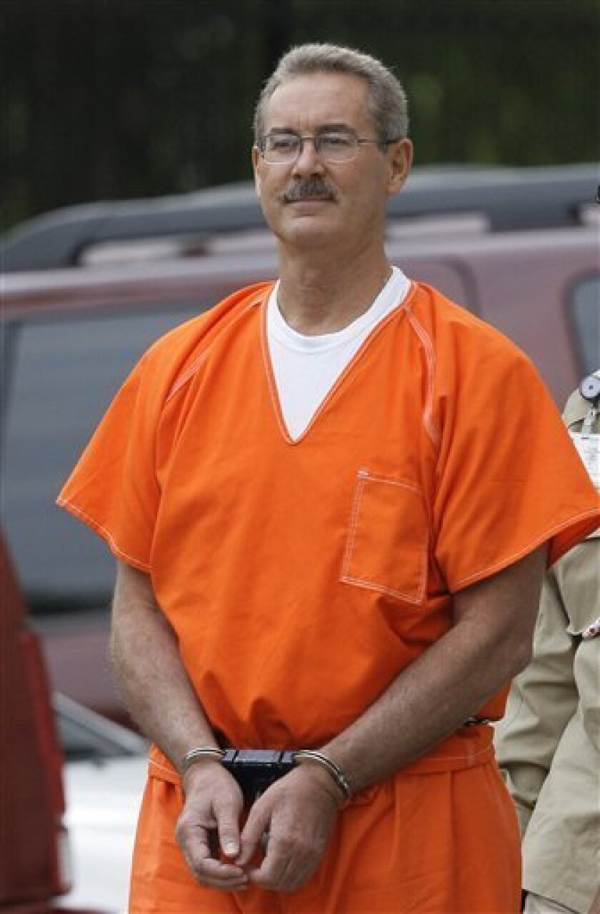 FILE - In this June 25, 2009 file photo, billionaire R. Allen Stanford is escorted into the federal courthouse in Houston. A federal judge on Friday, June 26 delayed releasing Stanford on bond until he can review a decision to allow the financier to be free until his trial on charges that he swindl
