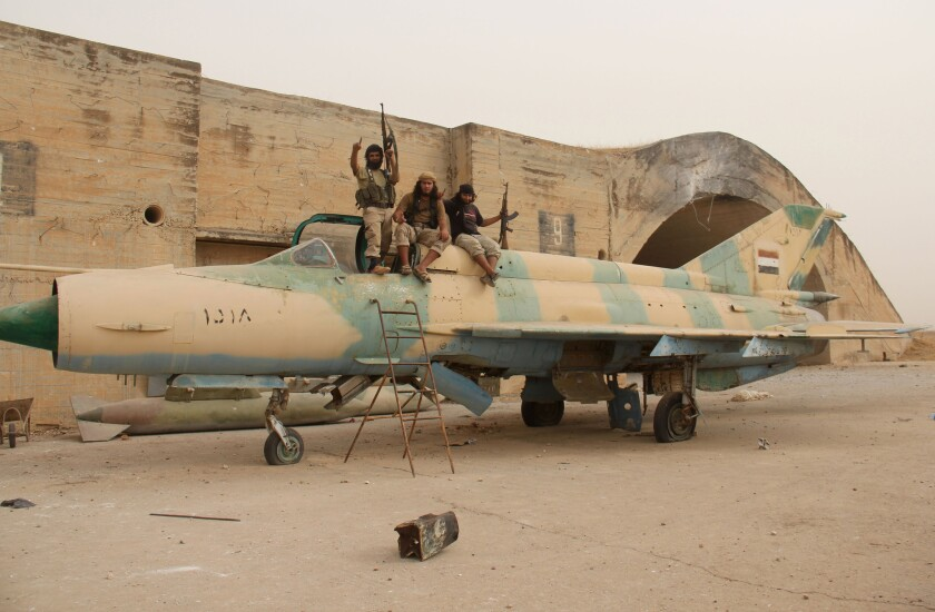 Members of Al-Qaeda's Syrian affiliate and its allies sit on top of a Syrian fighter jet after they seized the Abu Duhur military airport earlier this month.
