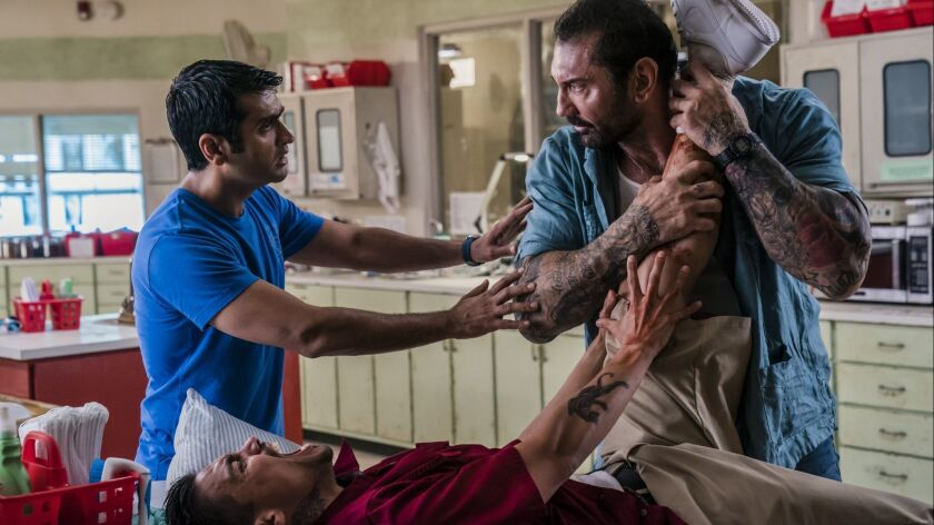"Kumail Nanjiani, left, Dave Bautista and Rene Moran (lying down) in ""Stuber."""