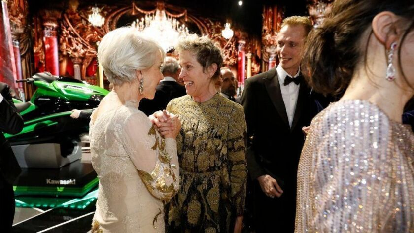 """Helen Mirren, left, congratulates lead actress winner Frances McDormand after the close of the 90th Oscars -- with the prize jet-powered ski in the background and """"The Shape of Water"""" star Doug Jones on the right."""