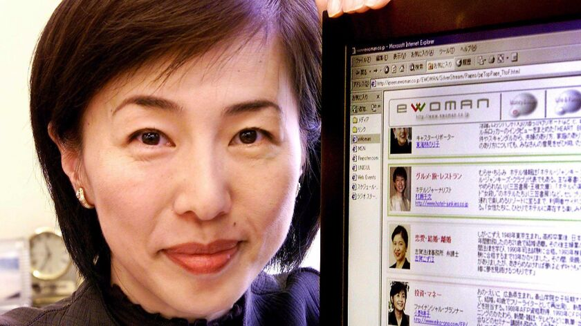 Japanese businesswoman Kaori Sasaki displays her company website at her office in Tokyo in 2000.