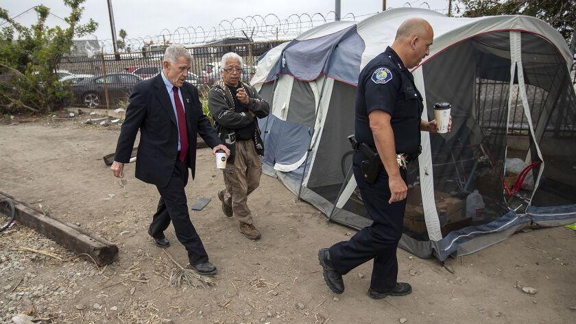U.S. District Judge David Carter, left, homeless activist Lou Noble and Deputy Chief Ken Gominsky of the Santa Ana Police Department walk past a tent along railroad tracks near Main Street in Santa Ana.