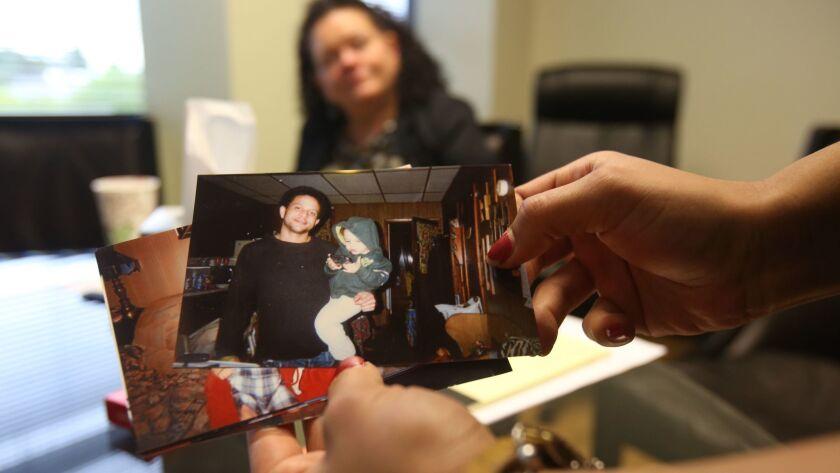 Brittany Glenn mira fotos de su hermano Brendon, quien fue baleado por un policía de Los Ángeles el año pasado, en Venice. La madre de ambos, Sheri Camprone, contempla desde atrás (Luis Sinco / Los Angeles Times).