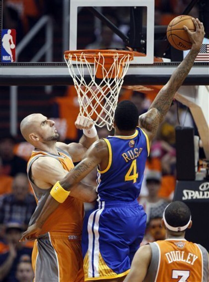 Golden State Warriors forward Brandon Rush (4) dunks the ball over Phoenix Suns center Marcin Gortat, left, of Poland, as forward Jared Dudley, right, watches in the second quarter of an NBA basketball game, Wednesday, Oct. 31, 2012, in Phoenix. (AP Photo/Paul Connors)