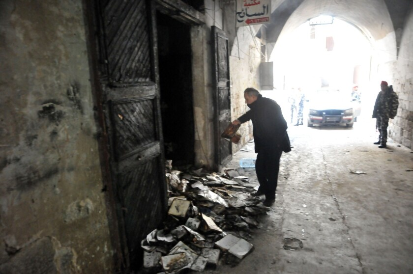 A man inspects burned books after an arson fire at the Saeh Library in Tripoli, Lebanon.