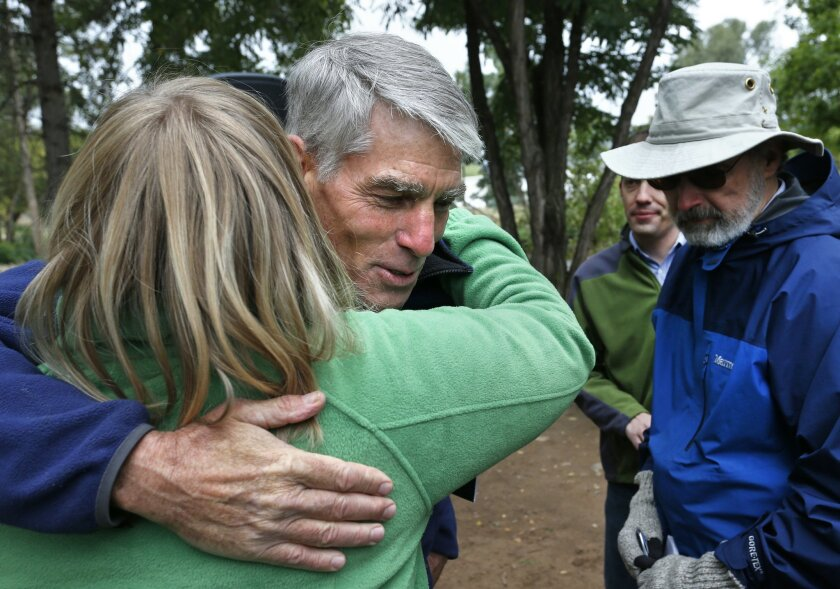 U.S. Sen. Mark Udall, D-Colo., hugs a supporter following a joint news conference with Trout Unlimited by the shore of the St. Vrain Creek, which was disastrously flooded a year ago this week, in Lyons, Colo., Friday, Sept. 12, 2014. The group spoke to mark the 50th year of the Land and Water Conservation Fund, a federal program which was created to use offshore oil and gas royalties to improve outdoor recreation opportunities and conserve irreplaceable lands. (AP Photo/Brennan Linsley)