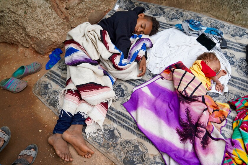 Hondurans Anthony Torres, 13, and his brother, Jose Alejandro, 3, sleep on blankets on the ground