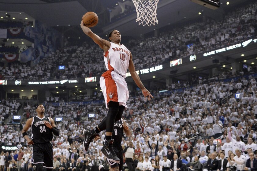 Toronto Raptors' DeMar DeRozan (10) goes up for a dunk as Brooklyn Nets' Paul Pierce (34) and Deron Williams (8) look on during the first half of Game 5 of the opening-round NBA basketball playoff series in Toronto, Wednesday, April 30, 2014. (AP Photo/The Canadian Press, Frank Gunn)