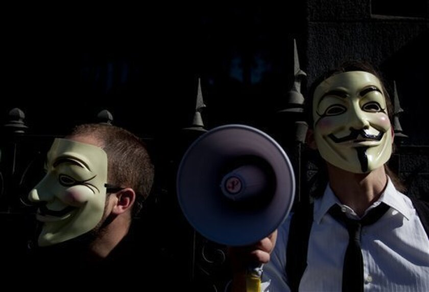 """File - In this May 15, 2011 file photo people wearing masks often used by a group that calls itself """"Anonymous"""" take part in a rally in Madrid. Spanish police arrested three suspected computer hackers that allegedly belonged to a loose-knit international activist group that has attacked corporate and government websites around the world, authorities said Friday June 10, 2011. A National Police statement identified the three detainees as leaders of the Spanish section of a group that calls itself """"Anonymous."""" (AP Photo/Arturo Rodriguez)"""