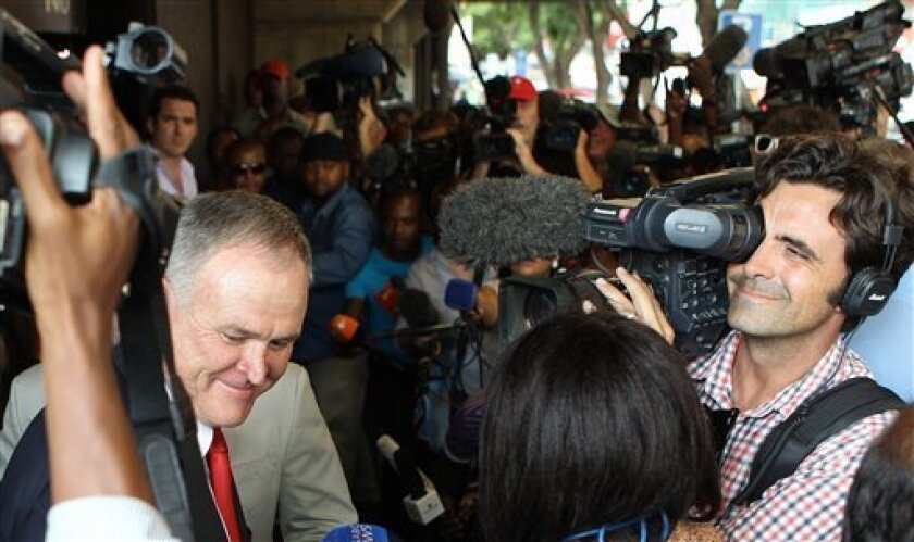 Advocate Barry Roux, left, avoids journalists as he leaves the court after representing Olympic athlete Oscar Pistorius for his bail application at the magistrate court in Pretoria, South Africa, Tuesday, Feb. 19, 2013.  Pistorius faces a bail hearing after charged with the shooting death of his gi