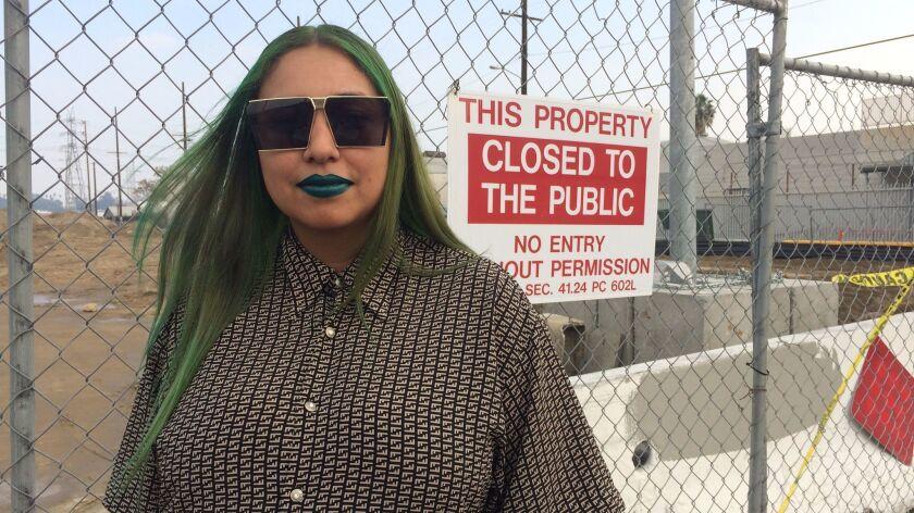 Artist Jazmin Urrea stands before a construction barricade at the 6th Street Bridge for Harry Gamboa Jr.'s fotonovela project.