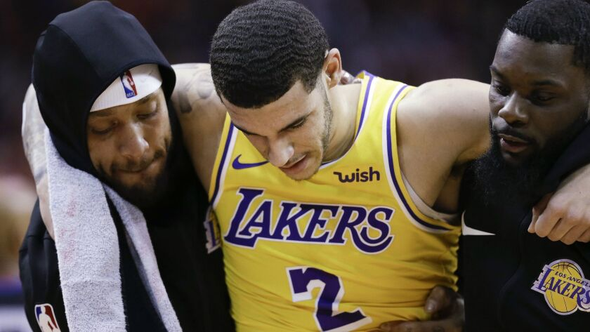 Lakers guard Lonzo Ball is carried off the court by Michael Beasley, left, and Lance Stephenson after Ball sustained an injury during the second half Saturday.