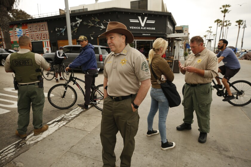 Sheriff Alex Villanueva stands on a sidewalk with cyclists and deputies behind him