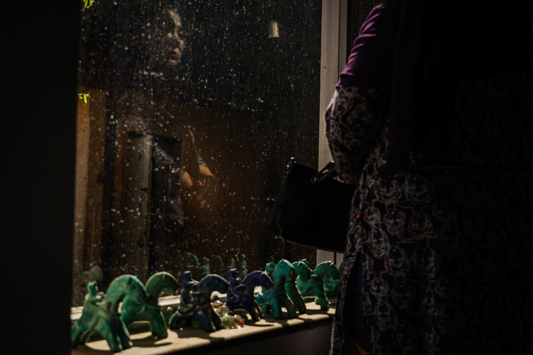 A woman weeps in front of a window.