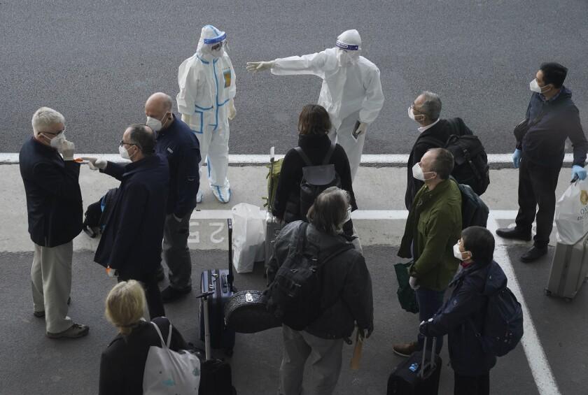 Un trabajador, equipado con un traje de protección, dirige a los miembros de un equipo de expertos de la Organización Mundial de la Salud a su llegada al aeropuerto de Wuhan, en la provincia de Hubei, en China, el 14 de enero de 2021. (AP Foto/Ng Han Guan)