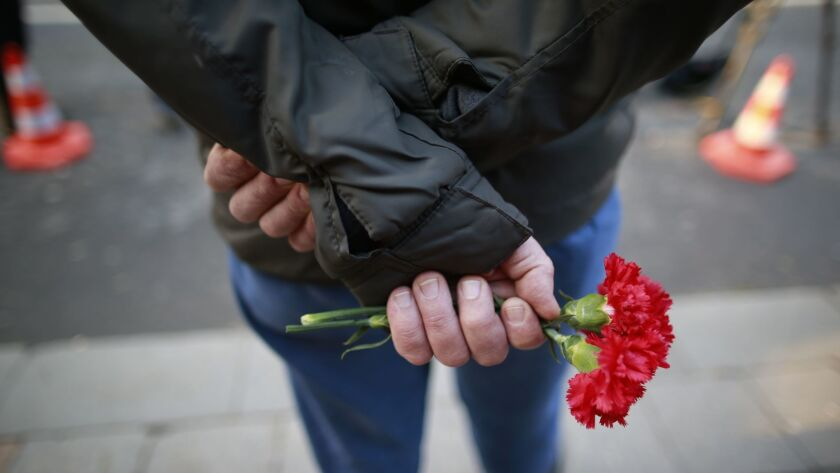 A man waits to leave a flower for the victims of a nightclub attack in Istanbul, Turkey.