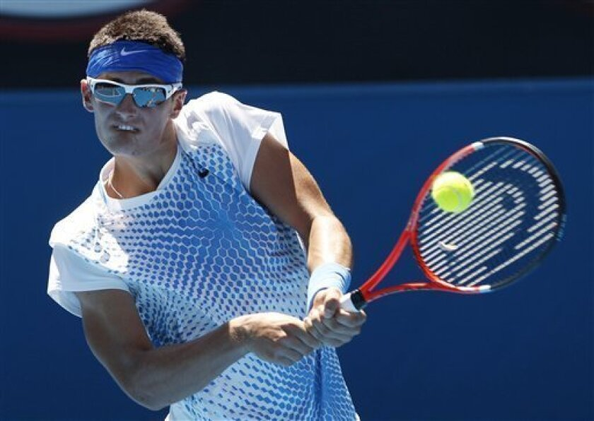 Bernard Tomic of Australia plays a backhand return to Feliciano Lopez of Spain during their second round match at the Australian Open tennis championships in Melbourne, Australia, Thursday, Jan. 20, 2011.   (AP Photo/Rob Griffith)