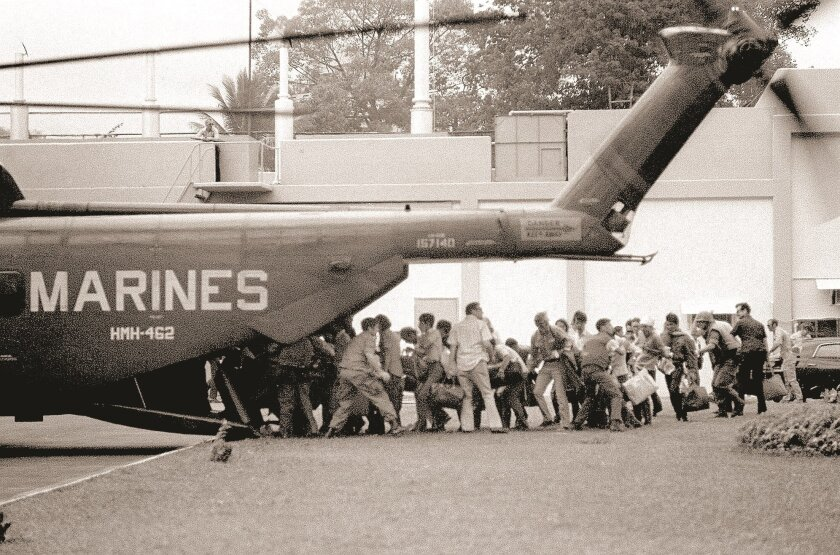 U.S. military and civilian personnel rush to board a Marine helicopter during the evacuation of the U.S. Embassy in Saigon, April 29, 1975.