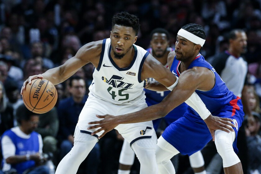 The Jazz's Donovan Mitchell is defended by Clippers' Maurice Harkless on Sunday at Staples Center.