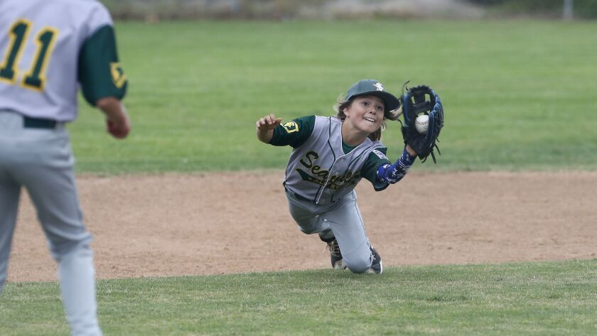 Seaview Little League's Carson Cato makes a diving catch against Costa Mesa National in a Little Lea