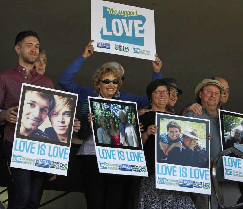 Supporters of same-sex marriage hold photos of themselves and their family members or partners at a federal courthouse in Eugene, Ore., last week.